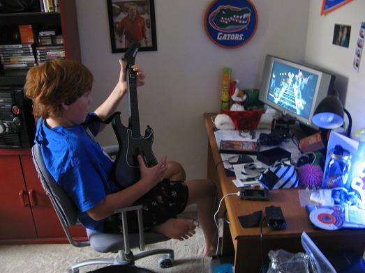 Playing Guitar Hero 3 the moment he wakes up the day after Christmas.JPG